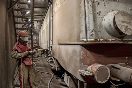 Two workers sandblasting a train cart in special protective suits, in a very big warehouse, designed to be a train service.