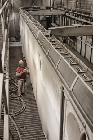A worker sandblasting a train cart in special protective suits, in a very big warehouse, designed to be a train service. Stock Photo