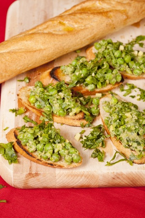 Bruschetta with green vegetables (peas, rocket, green salad) seasoned with parsley. All displayed with a baguette on a wooden cutting board and red fabric background.