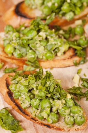 Bruschetta with green vegetables (peas, rocket, green salad) seasoned with parsley. All displayed on a wooden cutting board. Stock Photo