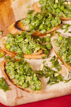 Bruschetta with green vegetables (peas, rocket, green salad) seasoned with parsley. All displayed on a wooden cutting board and red fabric background.