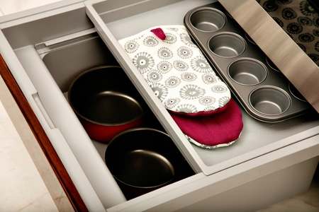 ingenious: A sliding kitchen drawer containing saucepans, oven mitts and a muffin tin.