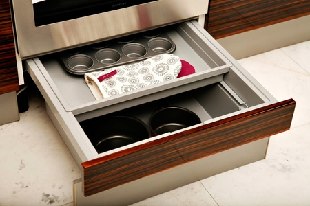 A sliding kitchen drawer containing saucepans, oven mitts and a muffin tin.