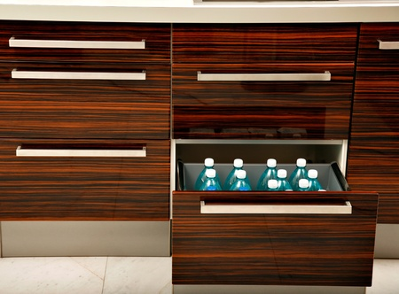 wenge: Drawer, part of kitchen furniture, especially designed for and containing water bottles.