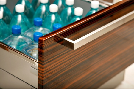 Drawer, part of kitchen furniture, especially designed for and containing water bottles.