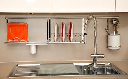 Modern kitchen sink with a few dishes, accessories and utensils. Stock Photo