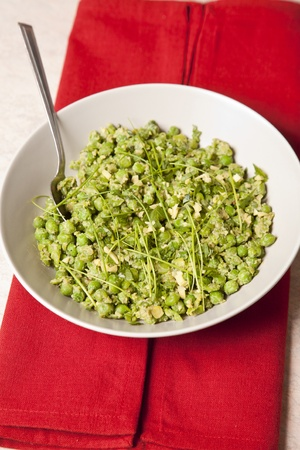 Healthy green vegetable salad served in a white dish. It contains peas, beans, rosemary and basil. All is displayed on a marble top.
