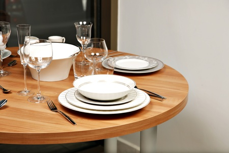 Round, wooden dining table with dishes and cutlery.