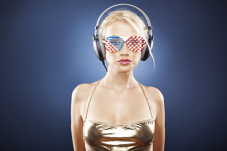 Beautiful blonde model with headphones and American inspired grid glasses dressed in gold swimwear.