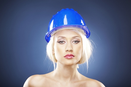Portrait of a beautiful blonde model with a construction helmet. Stock Photo