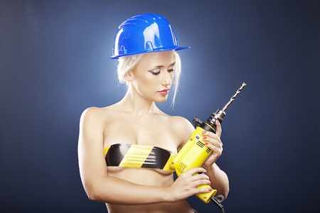 Beautiful topless model holds a power drill while wearing a blue construction helmet.