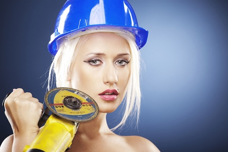 Beautiful topless model holds an angle grinder while wearing a blue construction helmet.