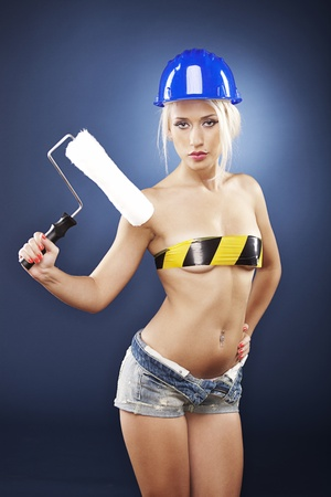 sexy topless women: Beautiful blonde model wearing short jeans and a construction helmet is holding a roller brush.