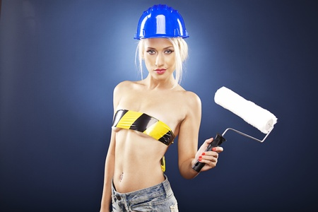 Beautiful blonde model wearing short jeans and a construction helmet is holding a roller brush.