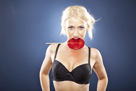 Beautiful blonde model, in black bra, bites into  a red lollipop.