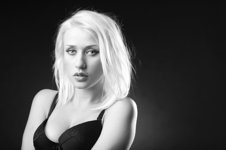 Black and white picture of a beautiful blonde model in a black bra. Stock Photo