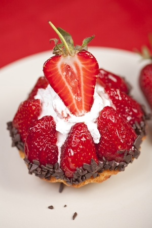 Delicious strawberry fruit tart with tiny chocolate shavings spred on the bottom and whip cream in the middle. Stock Photo