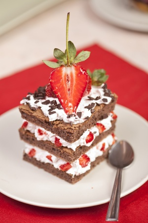 Chocolate strawberry cake with whipped cream on a white plate, beautifully decorated with chocolate shavings and strawberry halves on top. Stock Photo