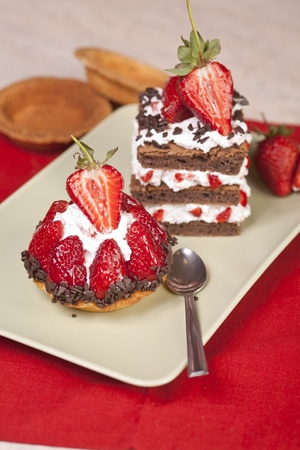 chocolate shavings: Strawberry fruit tart and chocolate strawberry cake on a plate. Both have whip cream and are beautifully decorated with chocolate shavings and strawberry halves on top. Stock Photo
