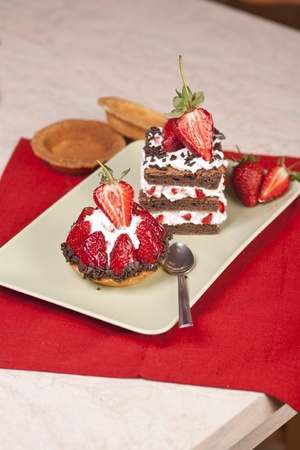 Strawberry fruit tart and chocolate strawberry cake on a plate. Both have whip cream and are beautifully decorated with chocolate shavings and strawberry halves on top. Stock Photo