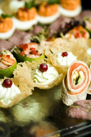 A mixt platou of gourmet miniatures aperitives. Includes salmon rolls, shrimp cocktails and lime, little baskets with cream cheese and beef file. Stock Photo