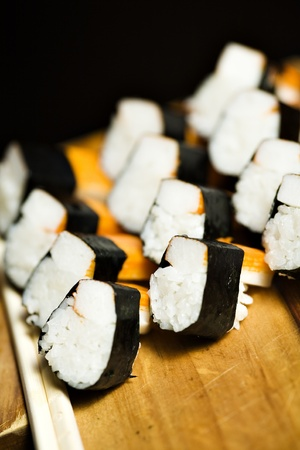 japanesse: A dozen of elegantly prepared surimi and rice in a sushi type roll, on a woody beige support. Stock Photo