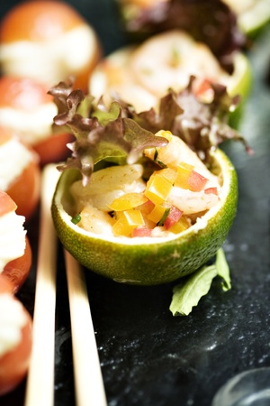 Lime basket filled with iceberg salad, very fine chopped vegetables, fruits and fish. Decorated with red and green salad and served on a asian inspired platou with sticks for service.