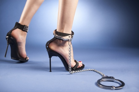 cuffs: A sexy womans ankles, wearing very high-heeled black sandals, with crystals applied and a ankle cuff around the right leg. Stock Photo