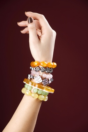 Model hand with fashionable amber bracelets, variatting in color, shape and design. Stock Photo