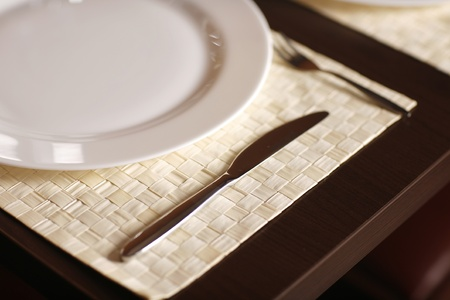 Close-up with a beautiful white plate and a sharp steak knife, in a lovely restaurant.