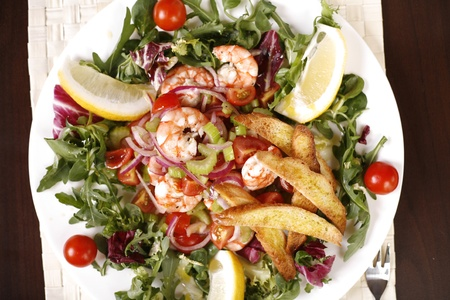 'baby spinach': View from the top of a exotic & colorful salad with shrimps, lemon slices, cherry tomatoes, celery, red onions, red cabbage, baby spinach and rucola.