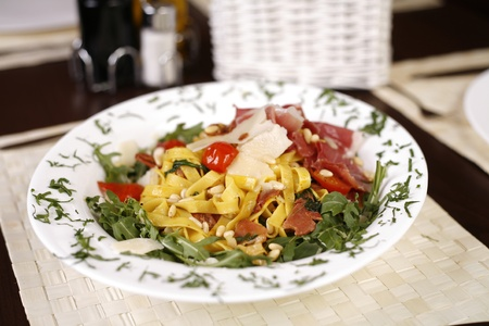 Beautiful dish of fresh taliagtelle with prosciutto, parmesan, sun dried tomatoes and fresh herbs on a elegantly set table. Stock Photo