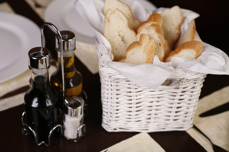 Elegant white basket with fresh bread next to a olivier with salt, pepper, olive oil and vinegar. Stock Photo
