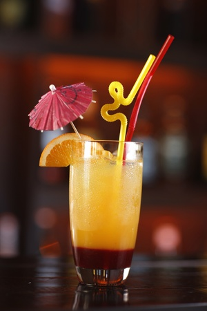 Beautiful glass with refreshing cocktail. Orange and dark red with two straws, a slice of orange and a pink umbrella. Stock Photo