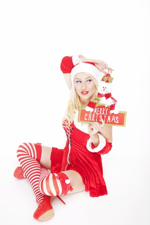 Beautiful blonde model, dressed in a Christmas outfit and holding a Christmas decoration, posing on a white background. Stock Photo