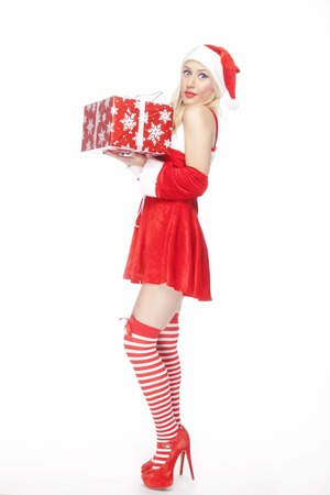 Beautiful blonde model, dressed in a Christmas outfit and holding neatly wrapped red present, posing on a white background.