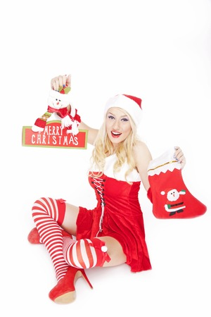 Beautiful blonde model, dressed in a Christmas outfit and holding a Christmas stocking & decoration, posing on a white background.