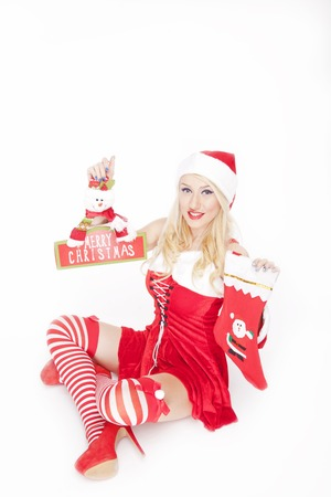 Beautiful blonde model, dressed in a Christmas outfit and holding a Christmas stocking  decoration, posing on a white background.