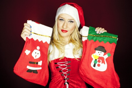 Beautiful blonde model dressed in Christmas outfit holding Christmas stockings, on a red background.