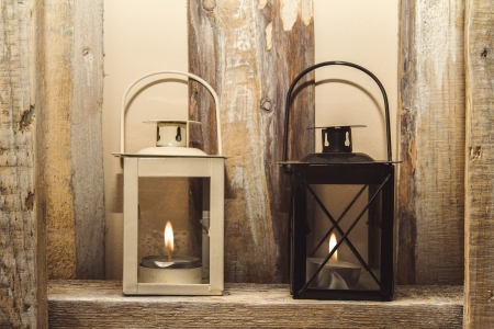 kerosene lamp: Two laterns on the old wooden wall Stock Photo