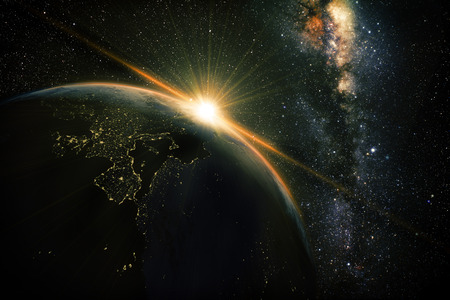world globe: sunrise view of earth from space with milky way galaxy