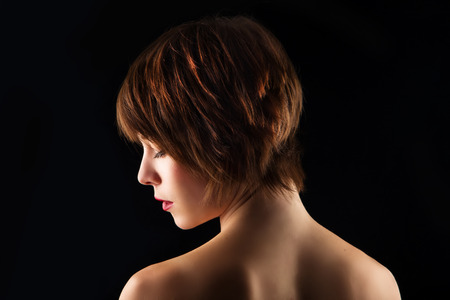 woman short hair: Side portrait of a young woman with short brown hair on a black background Stock Photo
