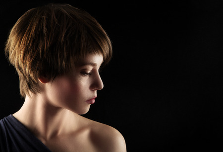 portrait de côté d'une jeune femme avec les cheveux bruns courts et les yeux bruns élogieux.