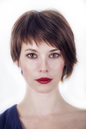 portrait d'une jeune femme avec les cheveux bruns courts sur un fond blanc