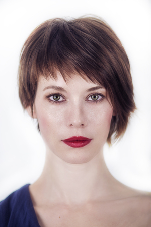 ritratto di una giovane donna con i capelli castani corti su uno sfondo bianco
