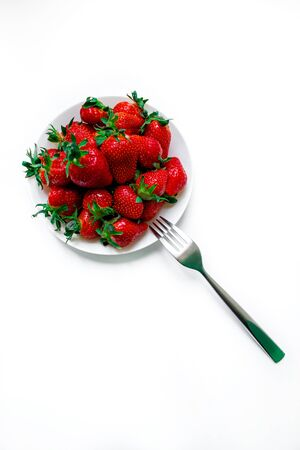 White plate with strawberries on a white background, and a fork. Beautiful still life. Tasty fruits.
