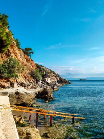 View of the Sea of Marmara. Rocks and brown stones of the island. Blue sky and shore. Prince Islands. Turkey. Beautiful horizontal photo, in good quality.