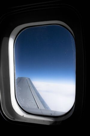 Aircraft porthole, with wing and blue sky. Flying above the clouds and the earth. High quality photo