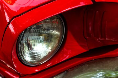 Front round headlight of a red retro car. Detail of an old vintage car. Modern tuning. High quality photo