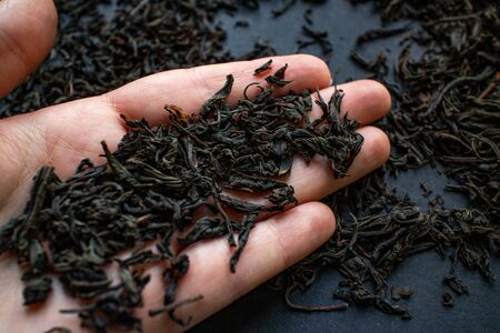 Delicious Ceylon, fresh, large leaf black tea on the fingers. Black background. High quality photo